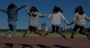 Group of young girls holding hands and jumping together happily.