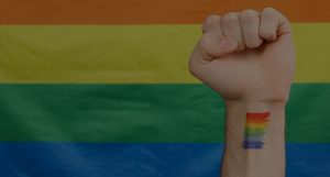 Fist in the air with a rainbow tattoo front of a multicoloured flag.